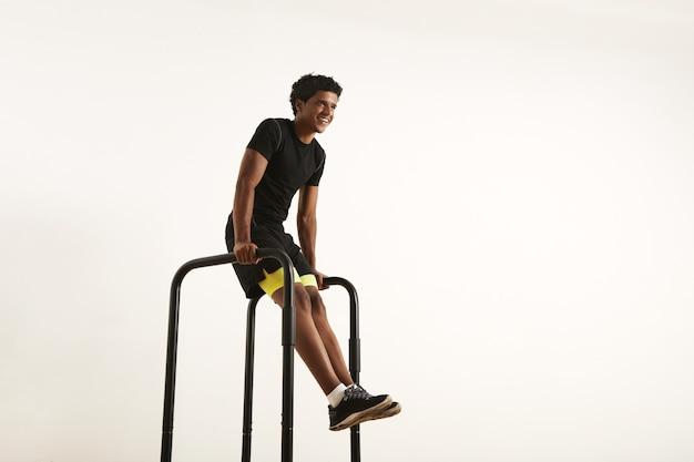 Sorrindo forte atleta afro-americano com um afro vestindo uma camisa sintética preta e shorts preto e amarelo fazendo l-senta-se em barras curtas em casa isolado no branco.