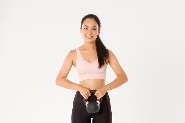 Sorrindo forte e magro garota asiática fitness, musculação em casa, segurando o equipamento de treino, agachamento com exercícios kettlebell, fundo branco.
