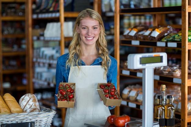 Sorrindo funcionários do sexo feminino segurando a caixa de tomate cereja no supermercado