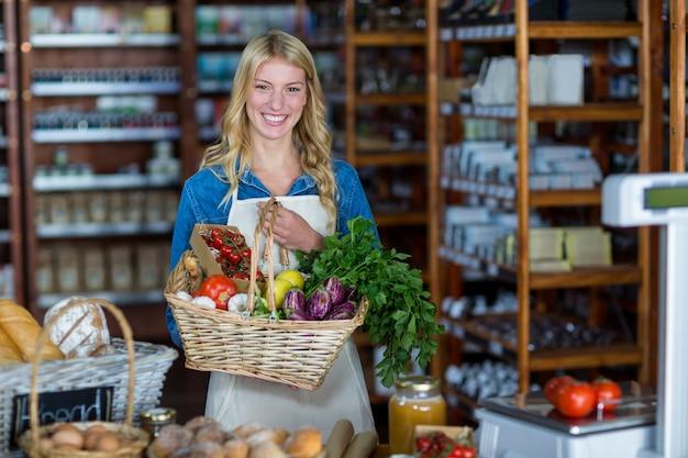 Sorrindo funcionários do sexo feminino segurando cesta de legumes na seção orgânica