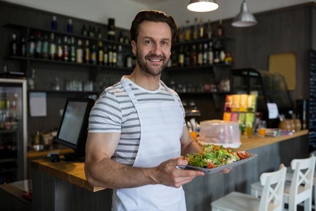 Sorrindo garçom carregando uma bandeja de salada no restaurante
