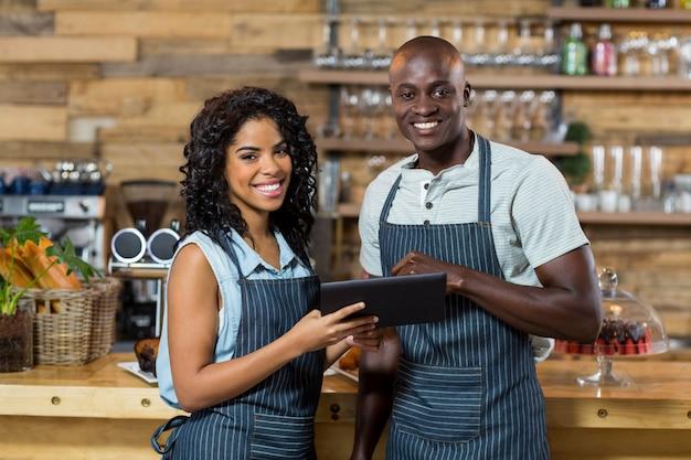 Sorrindo garçom e garçonete usando tablet digital no balcão no café