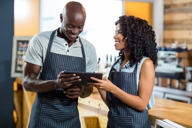 Sorrindo garçom e garçonete usando tablet digital no balcão