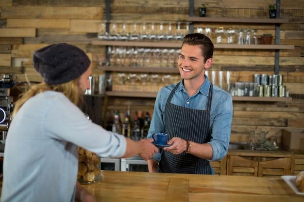 Sorrindo garçom servindo café para homem no balcão