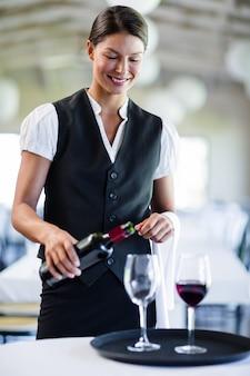 Sorrindo garçonete derramando vinho tinto em um copo
