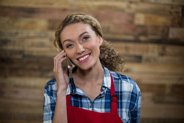 Sorrindo, garçonete, falando telefone móvel, contra, parede madeira