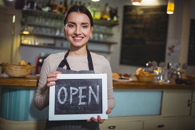 Sorrindo garçonete mostrando ardósia com sinal aberto no cafã ©