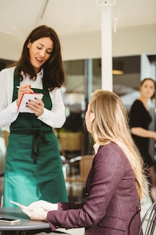 Sorrindo garçonete pegando um pedido no café