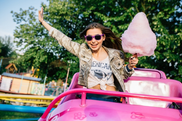 Sorrindo garota atraente em óculos de sol, montando uma montanha russa infantil