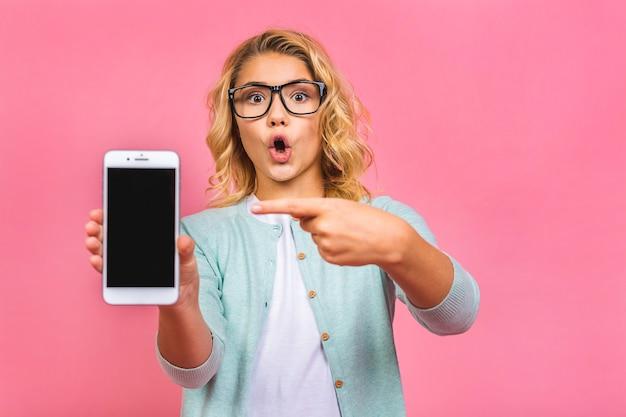 Sorrindo garotinha adolescente com telefone móvel com tela em branco vazia.