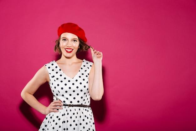Sorrindo gengibre mulher de vestido com o braço no quadril, olhando para a câmera sobre rosa