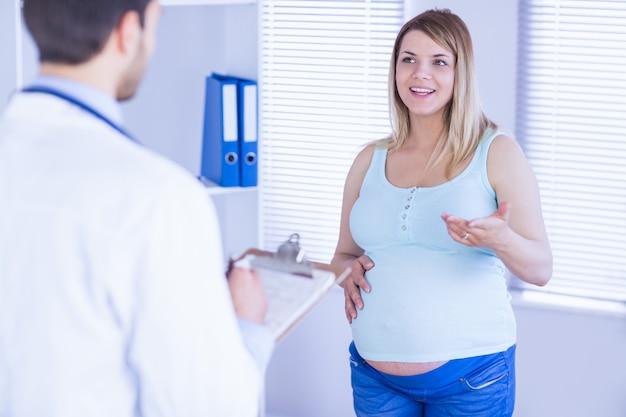Sorrindo grávida paciente falando com o médico que está tomando notas