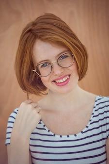 Sorrindo hipster de óculos em um de madeira