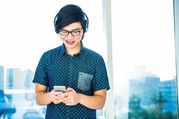 Sorrindo hipster empresário ouvir música em seu escritório
