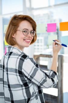 Sorrindo hipster mulher furando notas em um quadro de avisos no escritório