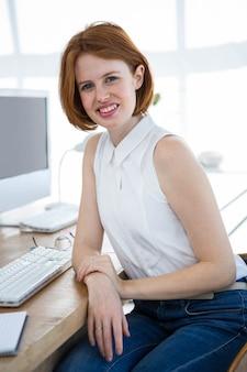 Sorrindo, hipster, mulher negócio, sentando, em, dela, escrivaninha escritório