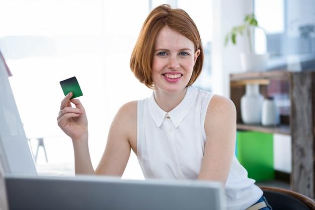 Sorrindo, hipster, mulher negócio, sentando, em, dela, escrivaninha, segurando, um, cartão crédito