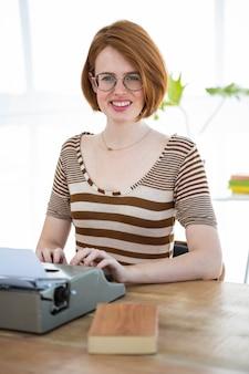 Sorrindo hipster mulher sentada em uma mesa, digitando na sua máquina de escrever