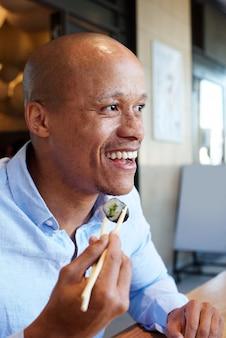 Sorrindo, homem africano, desfrutando, comendo sushi