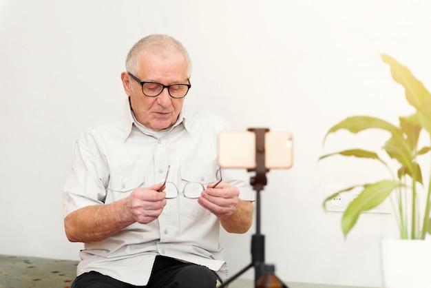 Sorrindo, homem ancião, olhando câmera, fazer, vídeo, blogue, ou, ligue casa, sentar sofá, namorando, headshot online, retrato