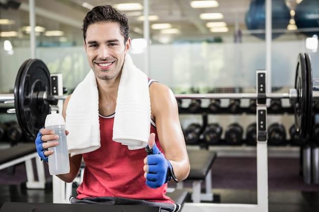 Sorrindo homem aparecendo o polegar e segurando a garrafa de água enquanto está sentado no banco