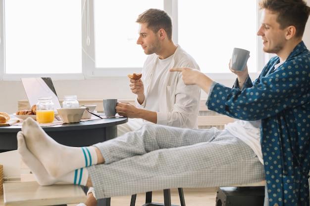 Sorrindo, homem apontando dedo, em, tela portátil, mostrando, algo, para, seu, amigo, comer, pequeno almoço