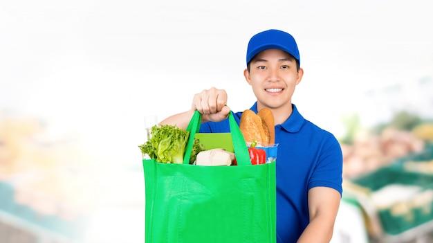 Sorrindo homem asiático segurando sacola de compras no supermercado, oferecendo serviço de entrega em domicílio