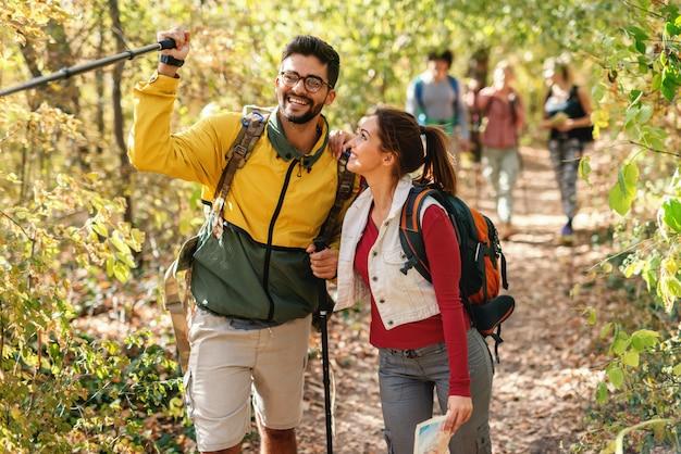 Sorrindo homem barbudo apontando para o caminho certo, enquanto a mulher inclinando-se sobre ele. caminhadas na floresta no conceito de outono.