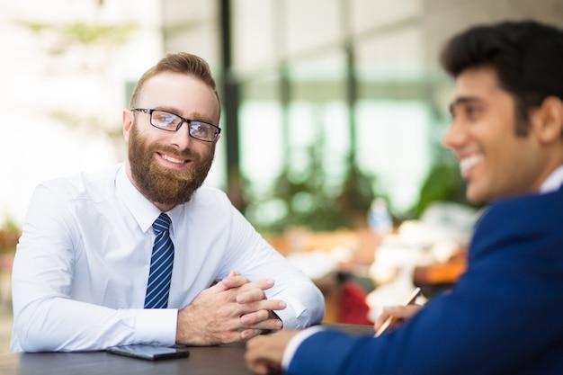Sorrindo homem barbudo bonito encontro com parceiro de negócios