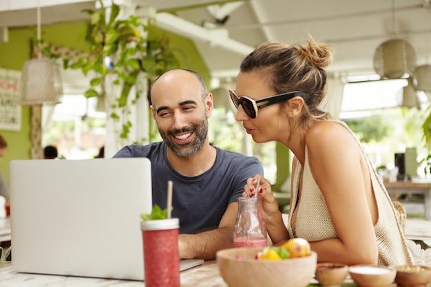 Sorrindo, homem barbudo e mulher de óculos escuros, sentado em frente ao laptop aberto e discutindo algo, olhando para a tela com interesse.