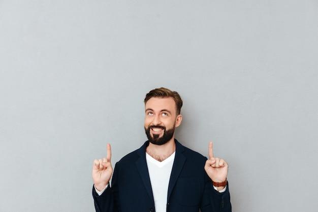 Sorrindo homem barbudo em roupas de negócios apontando e olhando para cima sobre cinza