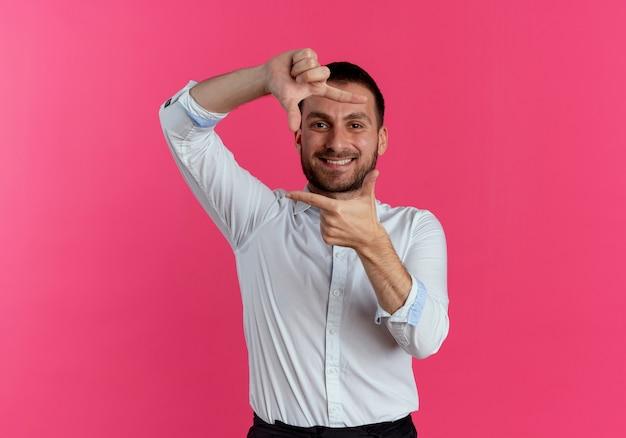 Sorrindo, homem bonito, gestos, quadro, mão, sinal, isolado na parede rosa