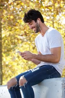 Sorrindo homem bonito sentado do lado de fora com fones de ouvido e telefone celular
