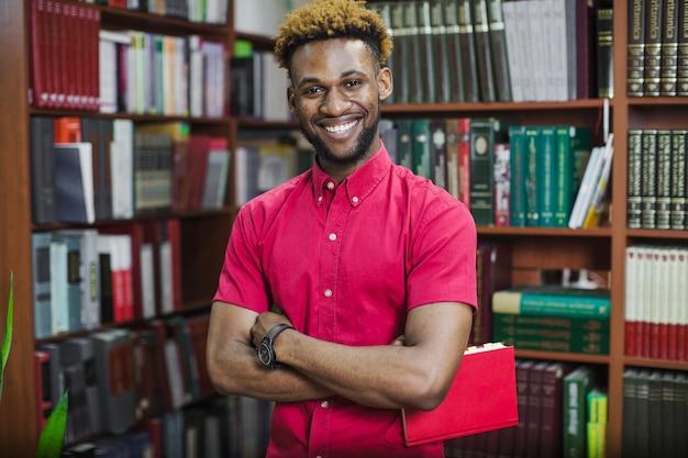 Sorrindo homem confiante com livro na biblioteca
