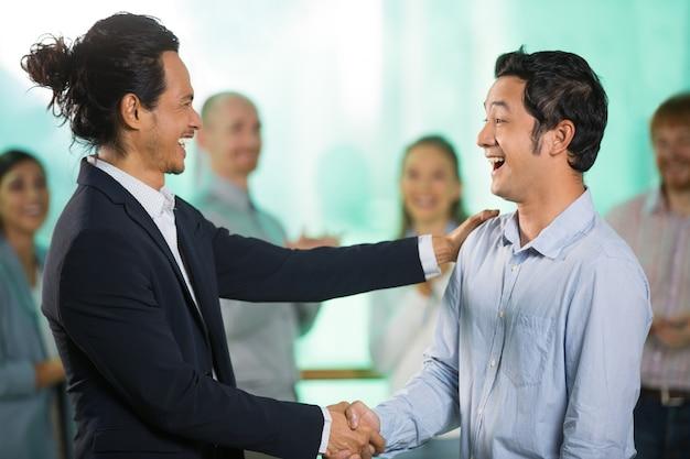 Sorrindo homem de negócio asiático cumprimento masculino parceiro
