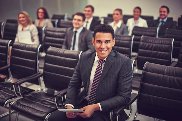 Sorrindo homem de negócios com os colegas de trabalho de fundo