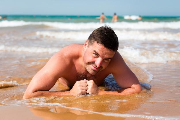 Sorrindo homem deitado na praia contra o mar