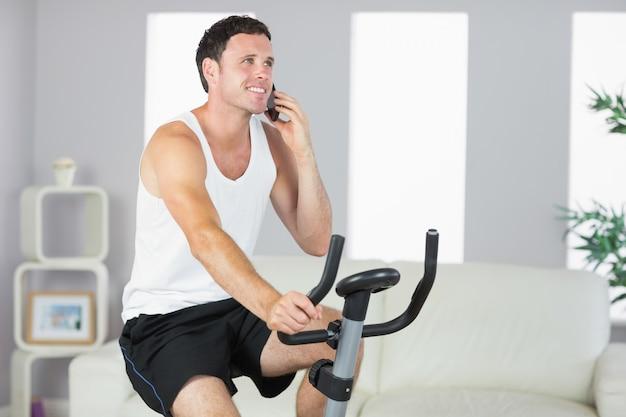 Sorrindo, homem desportivo, exercitando em bicicleta e telefonando