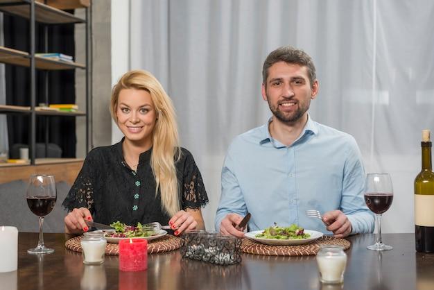 Sorrindo homem e mulher alegre perto de placas na mesa