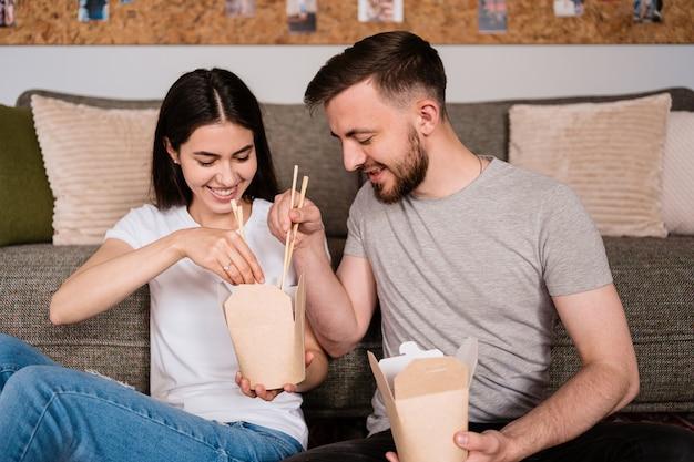 Sorrindo, homem e mulher almoçando juntos em casa