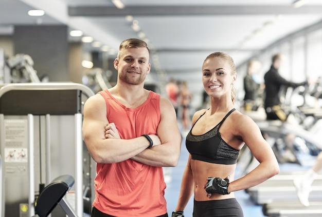 Sorrindo, homem e mulher no ginásio