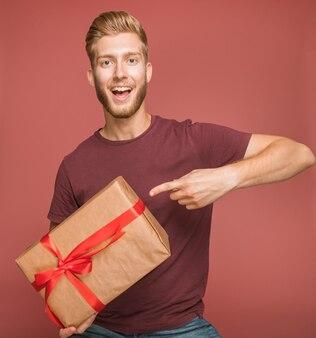 Sorrindo, homem jovem, apontar, dedo, embrulhado, caixa presente