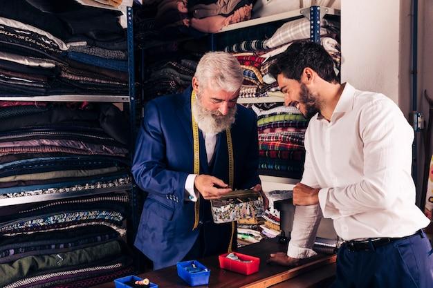 Sorrindo, homem jovem, e, sênior, alfaiate, selecionar, botão, de, a, recipiente, em, loja roupa