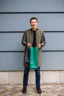 Sorrindo, homem jovem, ficar, contra, parede, segurando, bolsas para compras