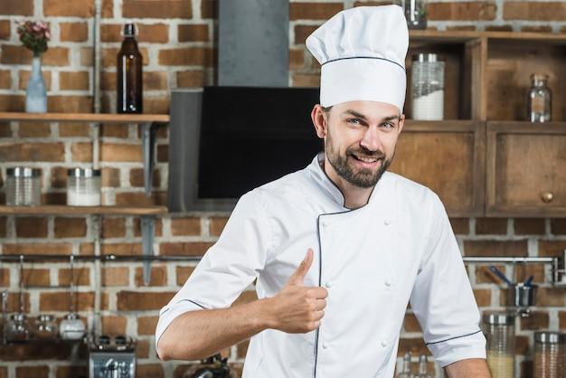 Sorrindo, homem jovem, ficar, em, cozinha, mostrando, polegar cima, sinal