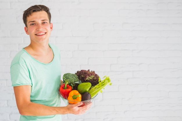 Sorrindo, homem jovem, ficar, frente, parede, segurando, coloridos, legumes frescos