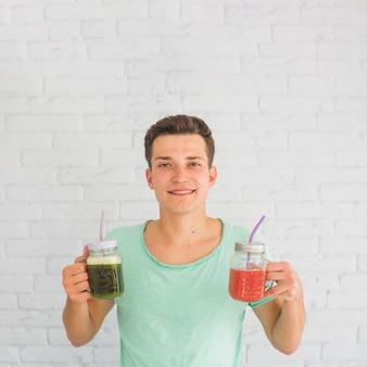 Sorrindo, homem jovem, ficar, frente, parede, segurando, verde vermelho, smoothie, frascos