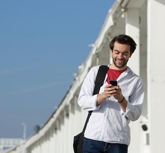 Sorrindo, homem jovem, leitura, mensagem texto, ligado, telefone móvel