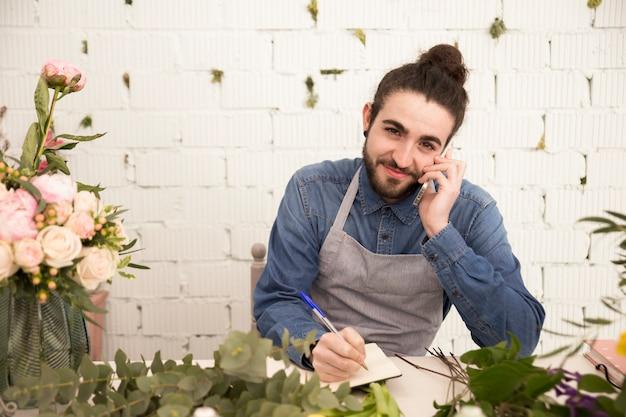 Sorrindo, homem jovem, levando, ordem, ligado, telefone móvel, em, a, loja florista