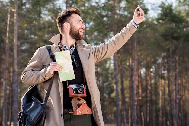 Sorrindo, homem jovem, segurando, mapa, em, mão, levando, selfie, em, a, floresta, com, telefone móvel